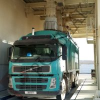 Bulk solids loading to open bulk trucks by loading chutes
